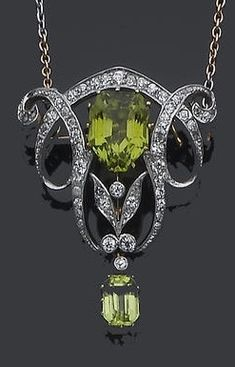 An Edwardian peridot and diamond brooch/pendant necklace, circa 1905. The mixed-cut peridot within an old brilliant and single-cut diamond scrolling foliate surround, suspending a step-cut peridot drop, the whole to a detachable bi-colour trace-link chain. #Edwardian #pendant