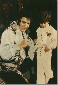 Elvis with a little fan on stage in 1975..... How cute