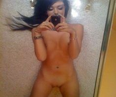 une belle brune se prend en photo  devant le miroir