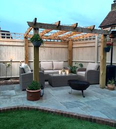 Rattan garden furniture placed under the pergola with fairy lights, plants and a fire pit to create the perfect cosy outdoor space! Backyard Patio Designs, Backyard Landscaping, Diy Patio, Landscaping Design, Garden Sitting Areas, Back Garden Design, Corner Garden, Corner Patio Ideas, Outdoor Pergola