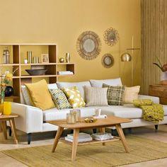 sala de estar decorada estilo moderno, colores para paredes, idea en color mostaza con sofá blanca con cojines, decoración con espejos, mesa de madera, tapete de mimbre