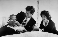 John F. Kennedy cuddling baby daughter Caroline as his wife Jacqueline looks on, March 1958