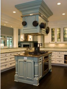 Love that all the cooking and baking is done in this island and the up draft vent is uniquely designed with a surrounding pot rack by alejandra