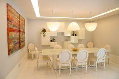 Sala de jantar | bem decorada |e iluminada | predominantemente branca | luminárias suspensas