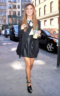 Ashley Tisdale in a chic blouse, trendy coat and matching skirt.