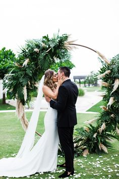 pampas grass and palm frond round wedding ceremony arbor