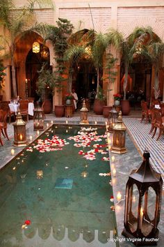 Marrakech Wedding, Credit Virginie Faucher, Moroccan pool with gold gilded lanterns, gorgeous arched architecture and floating flower petals.