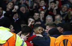 Rashford is mobbed by Manchester United supporters after scoring one of his two goals on a...