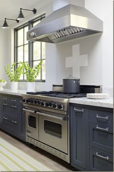 Love the dark gray/blue lower cabinets, nickel pulls and white walls.