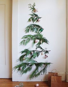 Or in place of a smaller tree, try attaching lots of boughs to the wall to make a flat but tall tree that can hold a few ornaments. | 15 Borderline Genius Christmas Decorating Ideas For Your Tiny Space
