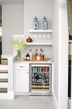 A clever redesign of the stairs during the reno created a few extra feet to squeeze in a self-serve bar. The open shelving keeps everyday dishes within reach and the kitchen airy.