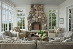 Fieldstone Fireplace flanked by windows,