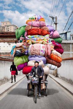 Que contiennent les baluchons en équilibre de ce vendeur ?/ Shangaï, China, Chine. / By Alain Delorme.