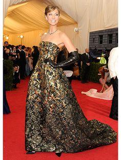 Karlie Kloss pulls off gloves on the red carpet.
