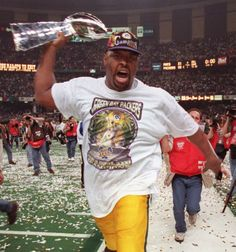 Reggie White screams with joy while carrying the Lombardi Trophy. - Image credit: Journal Sentinel files