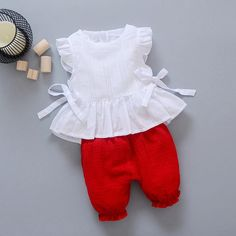 New Style 2017 Summer Baby Girls Clothes Sets Lace T Shirt Shorts 2 Pcs Infant Suits Comfortable Cotton Kids Casual SuitsGeorgia- Solid color two piece set. White sleeveless ruffle top with bow tie sides and layered lace ruffle bottom. Baby Girl Dress Patterns, Baby Dress Design, Frock Design, Kids Frocks Design, Baby Frocks Designs, Frocks For Girls, Toddler Girl Dresses, Cute Pants Outfits, Kids Outfits