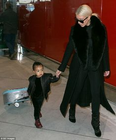 Jet-setter: North West pulled her own suitcase behind her as she arrived at Charles de Gaulle airport in Paris with her mother Kim Kardashian on Thursday
