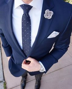 Nail that dapper look with a navy sportcoat and black dress pants. Black leather oxford shoes will instantly smarten up even the laziest of looks.   Shop this look on Lookastic: https://lookastic.com/men/looks/blazer-dress-shirt-dress-pants/20590   — White Dress Shirt  — Grey Floral Lapel Pin  — Navy Polka Dot Tie  — White Pocket Square  — Navy Blazer  — Silver Watch  — Black Dress Pants  — Black Leather Oxford Shoes