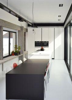 une cuisine moderne et blanche avec un îlot noir et des chaises rouges