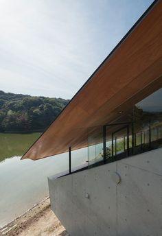 Een wonderlijk huis van Suppose Design Office in Fukuoka. Het is aan een meer gelegen maar toch blokkeert het enorme zadeldak het panorama. Met een kier tussen buitenmuren en dak wordt het uitzicht geregisseerd.  Photos  Toshiyuki Yano.