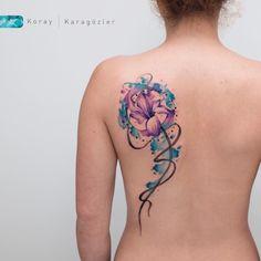 Tatuagem criada por KORAY KARAGÖZLER da Turquia.    Flor com fundo em tons de azul nas costas.
