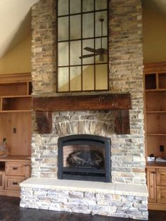 This light brown custom hand hewn mantel with corbels completes the look of this fireplace with class and dignity