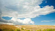 view over the meadows and hills in the summer sky with clouds - Stock Footage   by themanwhophoto