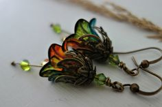 Fall flower earrings in orange and green with vintage bronze floral caps and peridot and topaz Swarovski crystal dangles. Beautiful for a woodland wedding or as a gift for her. Very pretty earrings.  The gentle breeze gives these light airy earrings a fluid movement that creates a true sense of freedom as they dangle and swing in the fresh air. Irresistibly feminine. My jewellery is exclusive to my little Etsy shop and stock is limited, so once it has gone it has gone.  Full drop 2 inches…
