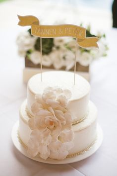 Simple two-tiered white wedding cake with customized banner cake topper - Photo by Jillian Mitchell