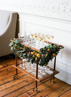 love this bar cart decorated with citrus + garland as a champagne bar!