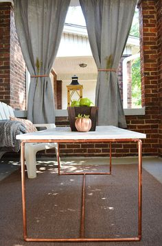 The centerpiece of these front porch fall decorations is a cool DIY copper pipe table. Here's the tutorial for the table and a look of the fall decorations.