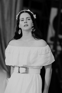 Lana Del Rey performing in a white dress and peace sign earrings
