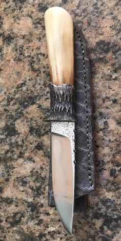 "This item is a custom made fixed blade knife by Howard Hitchmough. The blade is 3.5"" ats34, handle is fossil mammoth, the guard is hand cast silver and comes with a Great leather sheath. It is 7.75"" overall . It is also sporting a fabulous scrimshaw by Toi Skellern of S. Africa. Exquisite collectible or EDC knife. Brand new condition."