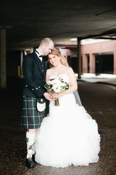 The Swords cuddle in a parking garage during couple portraits at Centennial Lakes Park in Minnesota.