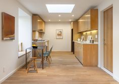 """White oak was also used for the kitchen cabinetry, and white marble for the countertops. In the open-plan dining area, another window seat pulls double duty as a bench for the kitchen table.  """"The bump-outs are designed to function as built-in furniture,"""" he says."""