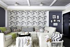 Basement family room features gray planked ceiling accented with box beams and flush mount lighting over accent wall clad in modern blue and gray floral wallpaper next to dark blue painted wall lined with eclectic art gallery framing a natural linen slipcovered U shaped sectional sofa adorned with navy chevron pillows and chartreuse throw blanket paired with a matching ottoman topped with black and gold lacquer tray alongside a vintage toy bin.