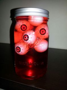 Mason jar, water, red food coloring, bag of zombie eyeballs from dollar store...halloween decoration, scary eyes in a jar