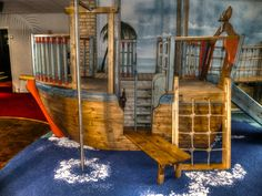 Pirate ship with fireman's pole (Smuggler's Bar and Grill restaurant indoor children's play area pirate themed with climbing ropes and slide)