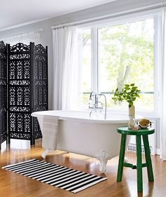 A bright bathroom with folding dividers and green stool with small plant