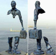 The suitcase is attached to his legs providing the support needed to hold up the rest of the statue.
