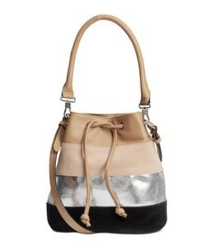 Block-patterned bucket bag in imitation leather with black and light beige panels in genuine suede. Drawstring, shoulder strap, and short, detachable handle at top. Three inner compartments, one with zip. Lined. Size 5 1/2 x 8 x 10 in.