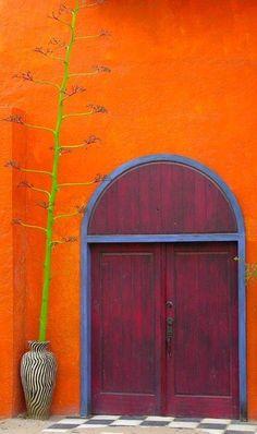 CincoDe orange wall w/huge red-brown door in Mexico.