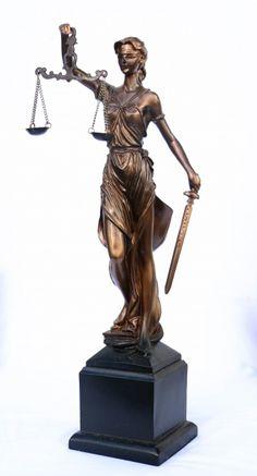 Grupo escultórico - Deusa da justiça executada em petit bronze com acabamento envernizado. Apresentada em posição típica segurando balança e espada. Sustentada sobre base quadrada. | Med. aproximada 30cm