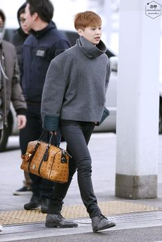 Xiumin, it's kinda weird to see him in a coat like this with a kind of girly bag haha