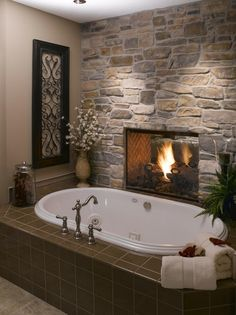 A stone wall with a see-through fireplace creates the backdrop for a lovely oval tub with a taupe tiled surround. Restful & romantic.
