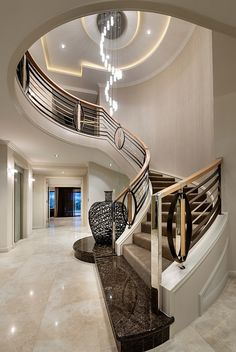 elegant entry with open curved staircase and banister in art deco style