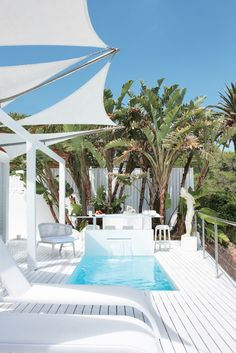 The White House. Third Beach, Clifton, Cape Town. A revamped beach bungalow by Jo'burg interior designer Stephen Rich. The wooden deck almost doubles the house's 160m2 area when the doors are opened up, creating plentiful space for entertaining and a water-feature bar.