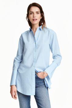 Chemise longue en coton: Chemise longue en coton tissé. Modèle avec petit col et boutonnage devant. Manches longues terminées par grand poignet ample avec bouton. Base arrondie avec fentes latérales et un peu plus de longueur dans le dos.