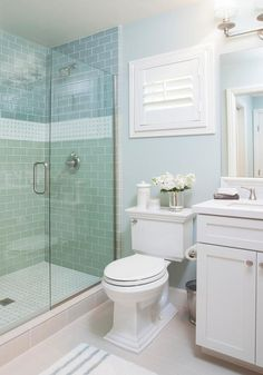 Blue cottage bathroom features a walk-in shower clad in blue subway tiles…