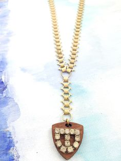 """Lean in for a Kiss"" - 1940's gold book chain paired with a wooden medallion accented with a 1940's rhinestone buckle"